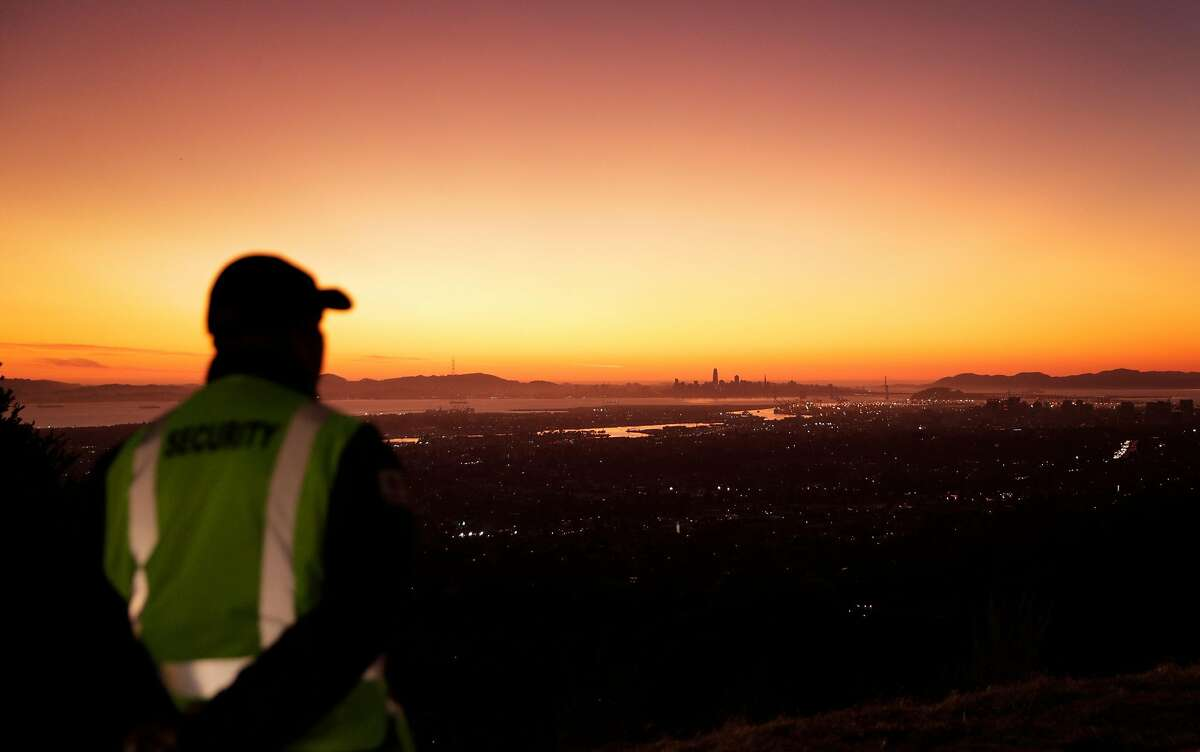 A security guard looks out over the Oakland hills in the parking lot of Merritt Community College at a Community Resource Center while waiting for power to be shut off in Oakland, Calif., on Wednesday, October 9, 2019. The utility's personnel there manage the public safety power shutoffs, which began last night and will continue throughout the day today as the Diablo winds begin to rise.