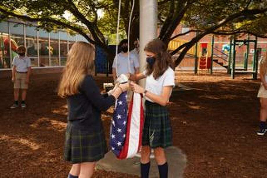 Eighth grade students lead a flag ceremony at St. Aloysius School as they keep a social distance from their masked peers. Lauren Smith, left, and Carielle D'Elisa unfold and raise the flag in the school courtyard at 33 South Ave. on Tuesday, Sept. 8. Photo: Grace Duffield / Hearst Connecticut Media