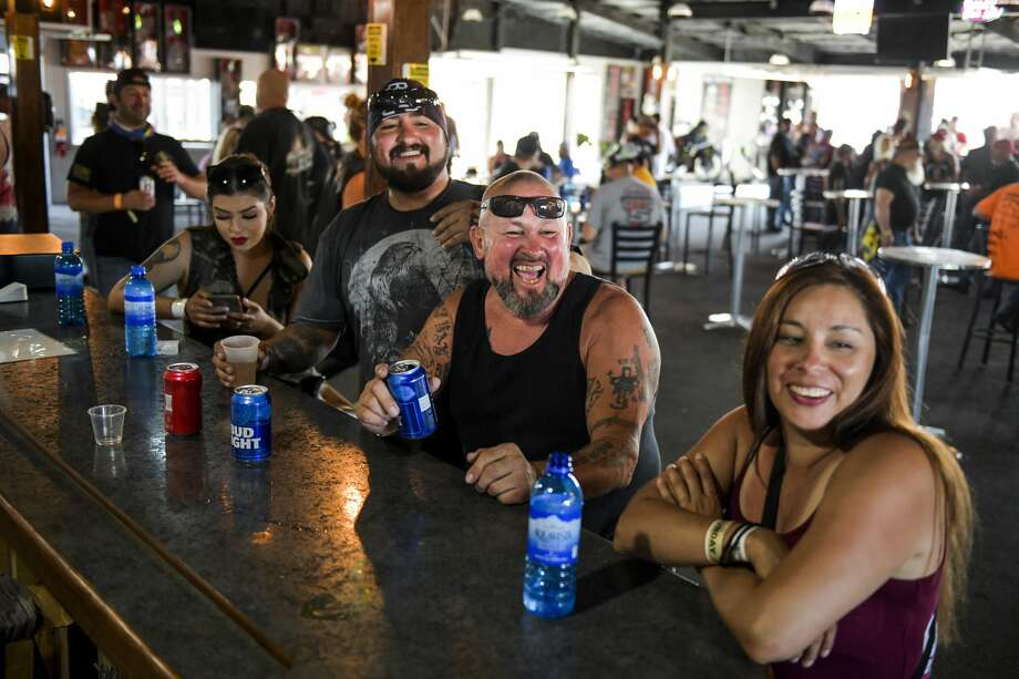 STURGIS, SD - AUGUST 09: Tonio Mondragon, second from left, Anthony Mondragon, second from right, and Cecily Romero, right, laugh while drinking at the Big Engine Bar at the Buffalo Chip during the 80th Annual Sturgis Motorcycle Rally in Sturgis, South Dakota on August 9, 2020. While the rally usually attracts around 500,000 people, officials estimate that more than 250,000 people may still show up to this year's festival despite the coronavirus pandemic. (Photo by Michael Ciaglo/Getty Images) Photo: Michael Ciaglo/Getty Images / 2020 Getty Images