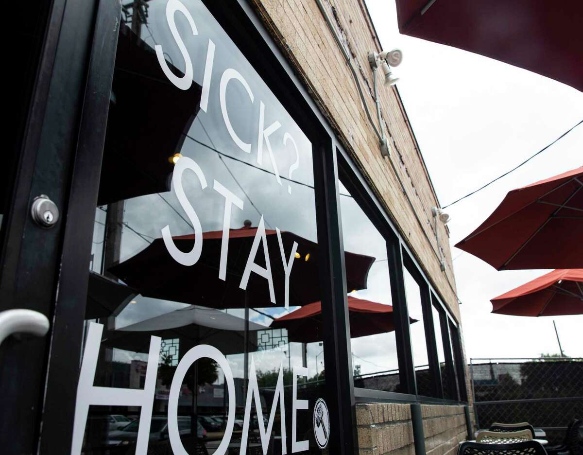 """A Houston coffeeshop displayed a """"Sick? Stay Home"""" sign on its window in July 20."""