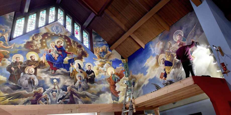 Paul Armesto of Queens, New York, paints the hands of St. John on an altar mural at Our Lady of Pompeii Church in East Haven in 2019, culminating four months of work on the project. Photo: Arnold Gold / Hearst Connecticut Media / New Haven Register