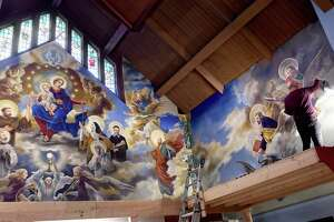 Paul Armesto of Queens, New York, paints the hands of St. John on an altar mural at Our Lady of Pompeii Church in East Haven in 2019, culminating four months of work on the project.