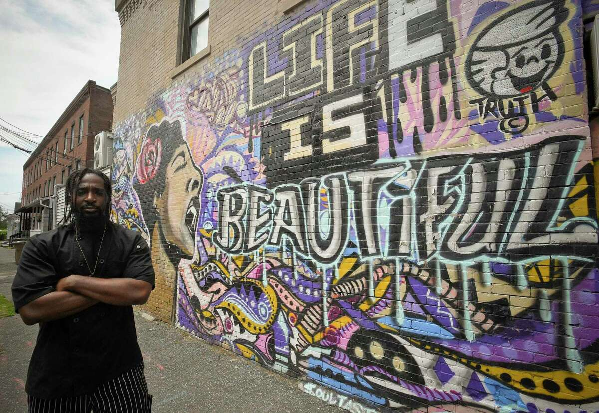Owner/Chef Jean Gabriel Jr. is seen next to a mural painted on the wall of Soul Tasty in Stamford in June 2020. We asked the talented Adae, who has a mural along the Farmington Canal Trail in New Haven, about this form of art. He said he's inspired to contribute to