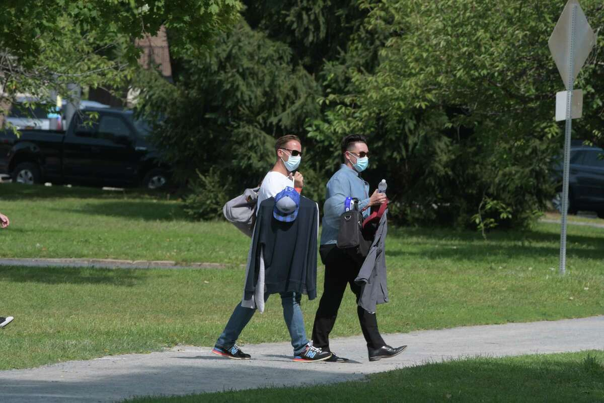 Crew members of the television show Modern Love carry in wardrobe as they prepare to film a scene at Washington Park on Wednesday, Sept. 9, 2020, in Albany, N.Y. (Paul Buckowski/Times Union)