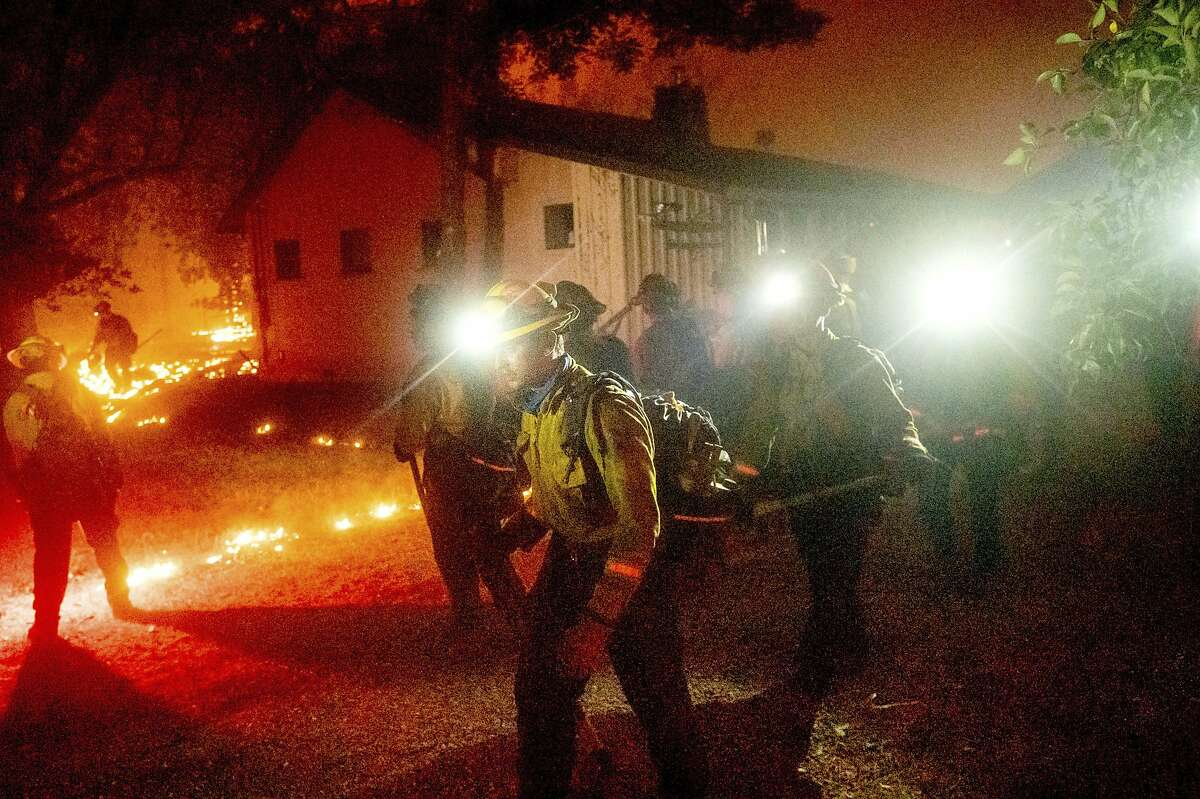 A hand crew works to save a home as the Bear Fire burns through the Berry Creek area of Butte County, Calif., on Wednesday, Sept. 9, 2020. The blaze, part of the lightning-sparked North Complex, expanded at a critical rate of spread as winds buffeted the region. (AP Photo/Noah Berger)
