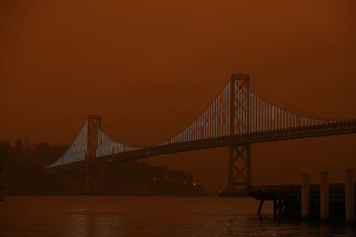 The Bay Bridge is seen under a sky glowing orange due to smoke from the wildfires on Wednesday, September 9, 2020 in San Francisco, Calif.