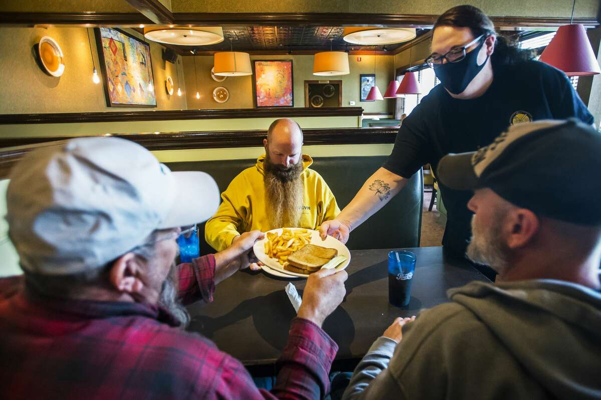 Sara Morrow, right, serves dishes to Marty Osinski, left, Scott Harper, center, and Matt Prior, right, as they have lunch at the new location of Alex's Railside Restaurant inside Midland Mall on its opening day, Wednesday, Sept. 9, 2020. (Katy Kildee/kkildee@mdn.net)