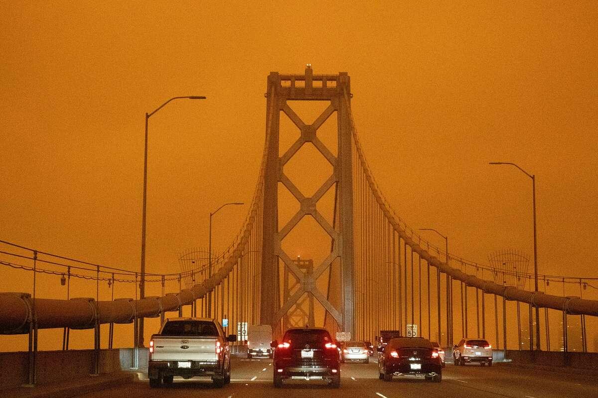 Dark orange skies hang over the Bay Bridge in San Francisco, Calif. Wednesday, September 9, 2020 due to multiple wildfires burning across California and Oregon.