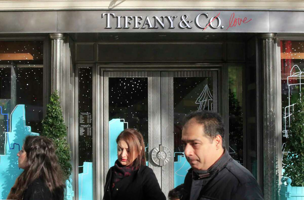 FILE - In this Nov.25, 2019 file photo, people walk past a Tiffany jeweler shop on the Champs Elysees avenue in Paris. LVMH is ending its monthslong pursuit of luxury jewelry retailer Tiffany & Co., citing in part the impact of proposed tariffs on French goods. The Paris-based conglomerate said that it needs more time to assess the impact of U.S. tariffs on French goods and cannot close the deal before year-end. (AP Photo/Michel Euler, File)