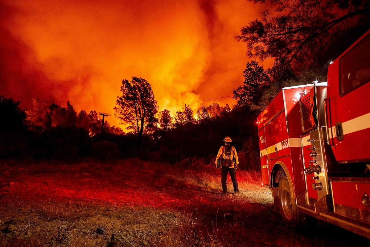 Butte county firefighters watch as flames tower over their truck at the Bear fire in Oroville, California on September 9, 2020. - Dangerous dry winds whipped up California's record-breaking wildfires and ignited new blazes, as hundreds were evacuated by helicopter and tens of thousands were plunged into darkness by power outages across the western United States. (Photo by JOSH EDELSON / AFP) (Photo by JOSH EDELSON/AFP via Getty Images)