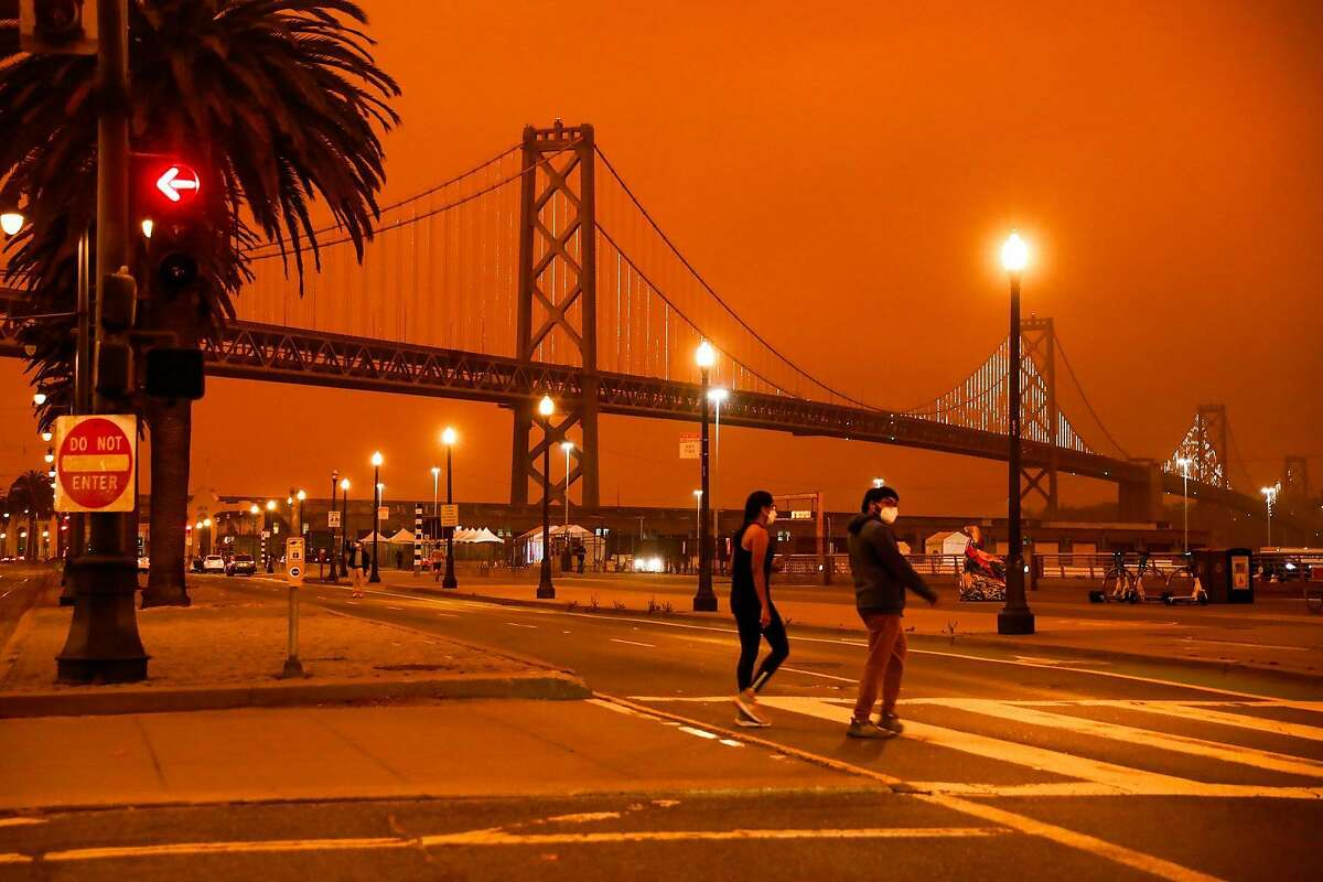 People pass by the Bay Bridge as dark orange skies hang over downtown San Francisco, Calif. Wednesday, September 9, 2020 due to multiple wildfires burning across California and Oregon.
