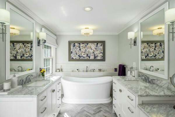 The master bath received an $85,000-plus update including a soaking tub, glass shower, double vanities with quartzite counters and flooring arranged in a herringbone pattern.