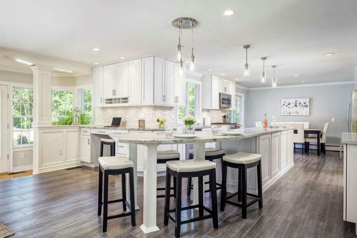 Features in the kitchen, which was renovated in 2014, include a long center island/breakfast bar, an eat-in area, quartzite counters, a marble backsplash, and provides access to the expansive deck.