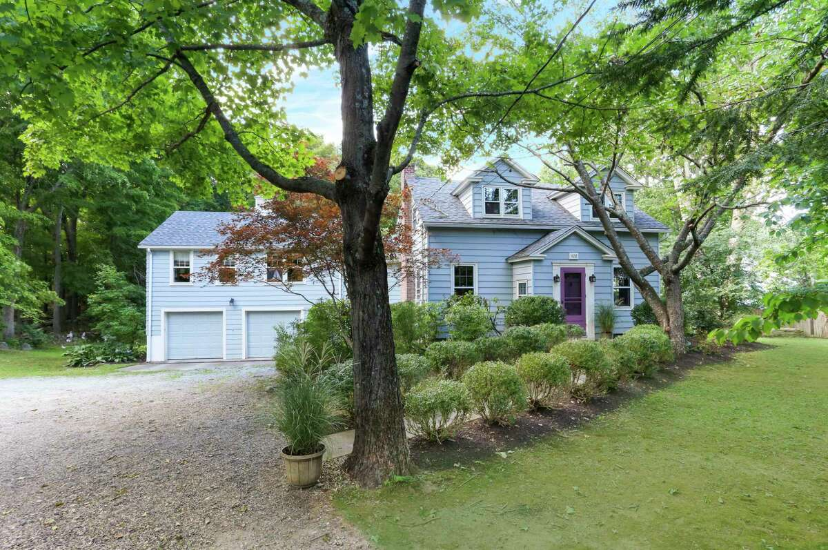 The light gray colonial Cape Cod at 428 Westport Road in Easton sits on a 1.72-acre level property.