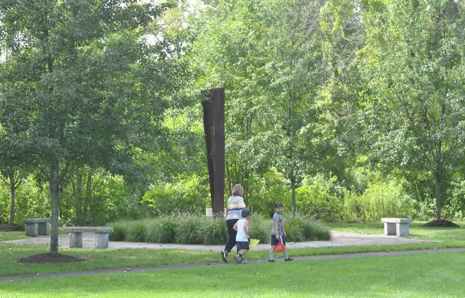 A family on the walking path around the Recreation Center property pass the 9/11 monument on Friday, Sept. 4. Photo: Macklin Reid / Hearst Connecticut Media