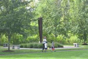 A family on the walking path around the Recreation Center property pass the 9/11 monument on Friday, Sept. 4.