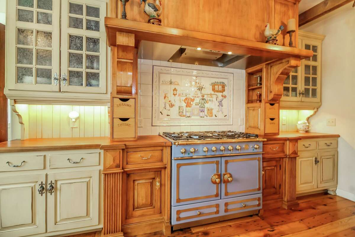The state-of-the-art chef's kitchen features a food pantry, coffee station, quartz countertops, farm sink, hand-painted ceramic tile backsplash, red brick gas fireplace, and a French LaCornue range.