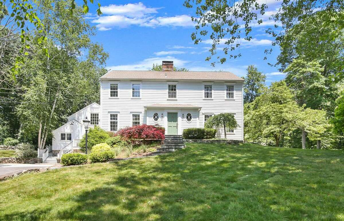 """The 4,508-square-foot colonial house at 14 Sunset Drive sits on a two-acre level and lightly wooded property in Lower Weston. This 11-room home, originally built in 1969, sits high on a landscaped lot. """"Enjoy summer evenings on the stone patio overlooking the expansive backyard with a fire pit and a plentiful organic garden,"""" the co-listing agents said. """"Feel right at home from the moment you enter this beautiful, light-filled colonial,"""" they said. The paved driveway widens closer to the house and the attached, under house two-car garage, and this gravel area, bordered by fieldstone walls, provides ample parking. Climb the stone steps to the front entrance, where the sage-colored front door is flanked by lanterns and elliptical windows and opens into the good-sized foyer revealing an open concept floor plan. Three tall columns stand between the foyer and the formal living and dining rooms."""
