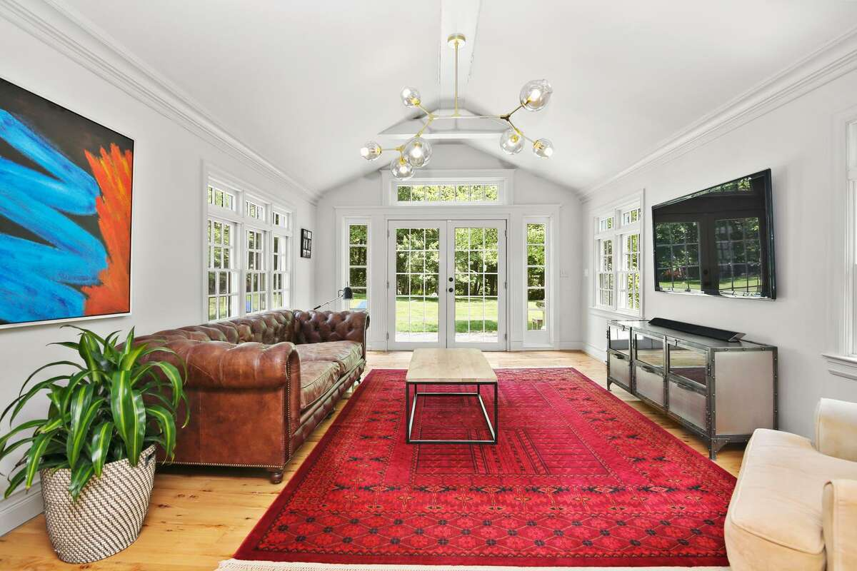 """The sunroom has a cathedral ceiling and French doors to the expansive paving stone patio and backyard. This versatile room could also serve as a second home office, if necessary. The living room has a large, multi-pane """"walk-in"""" bay/bow window. In the dining room there is a fireplace and wainscoting framing the lower walls. Its mantel features dentil molding. Off the living room there is a sunroom with a cathedral ceiling and French doors to the expansive paving stone patio and backyard. This versatile room could also serve as a home office."""
