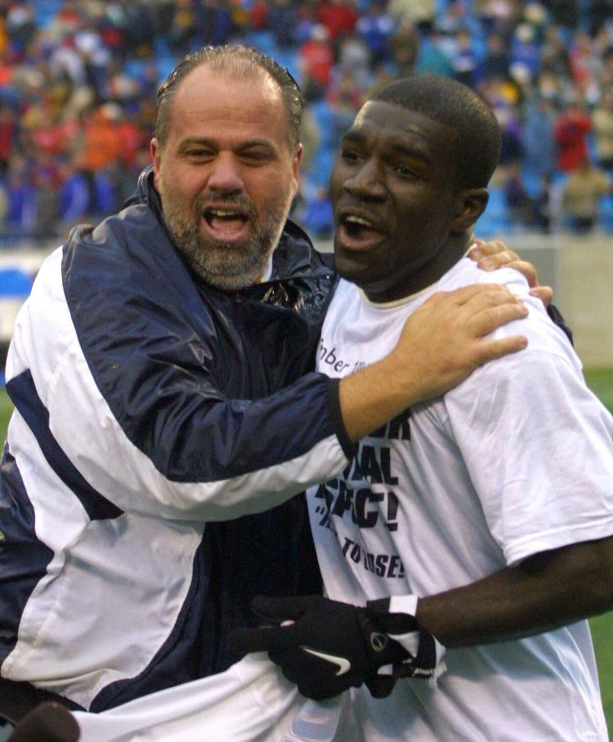 UConn men's soccer coach Ray Reid, left, celebrates with Chris Gbandi after winning the NCAA championship game against Creighton in 2000. Reid is creating an endowment to help minority soccer coaches get more educational coaching experience.