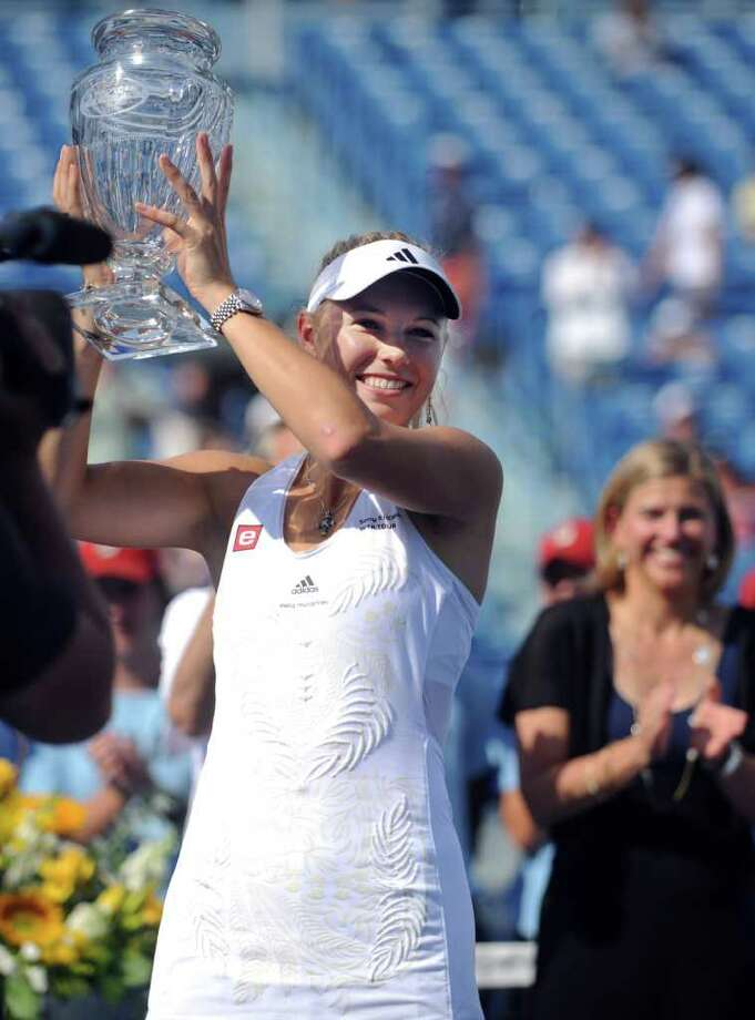 Caroline Wozniacki holds up the championship trophy following her third consecutive Pilot Pen victory after defeating Nadia Petrova in the women's final Saturday August 28, 2010 at the Connecticut Tennis Center in New Haven. Photo: Autumn Driscoll / Connecticut Post