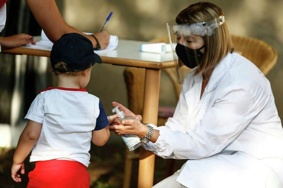A boy get his hands sanitized on the first day of school as daycares and nursery schools reopened in Rome after months of closure due to the coronavirus pandemic, on Wednesday, Sept. 9, 2020. (Cecilia Fabiano/LaPresse via AP) / LaPresse