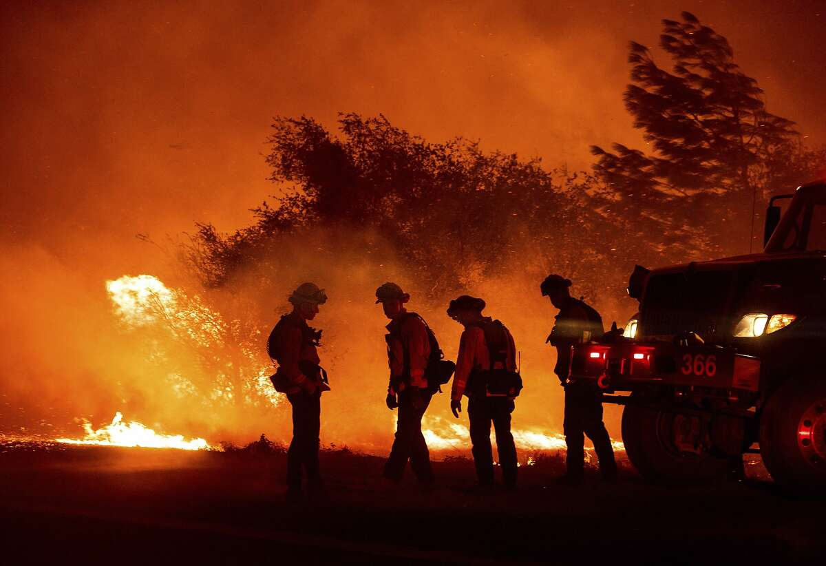 Firefighters monitor the Bear Fire burning in Oroville, Calif., on Wednesday, Sept. 9, 2020. The blaze, part of the lightning-sparked North Complex, expanded at a critical rate of spread as winds buffeted the region. (AP Photo/Noah Berger)