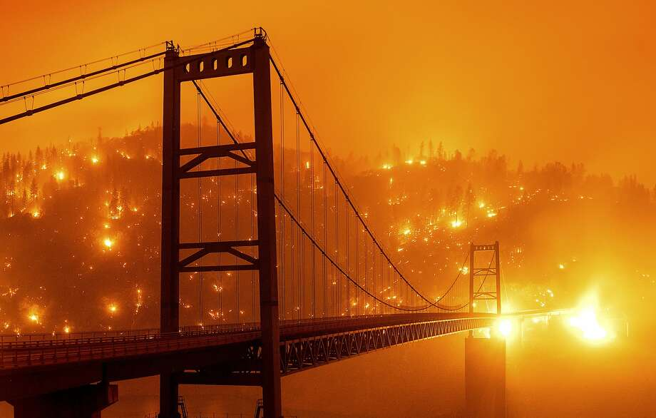 In this image taken with a slow shutter speed, embers light up a hillside behind the Bidwell Bar Bridge as the Bear Fire burns in Oroville, Calif., on Wednesday, Sept. 9, 2020. The blaze, part of the lightning-sparked North Complex, expanded at a critical rate of spread as winds buffeted the region. (AP Photo/Noah Berger) Photo: Noah Berger / Associated Press