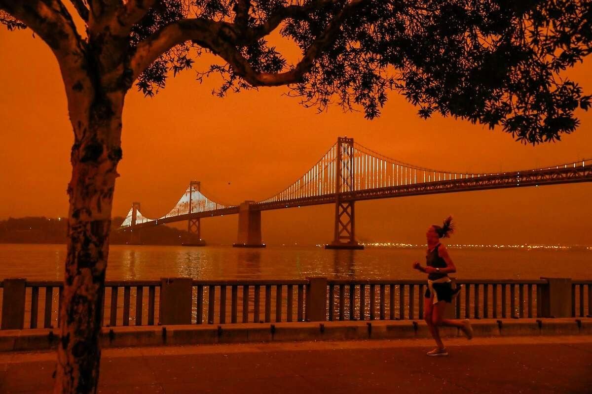 A woman jogs by the Bay Bridge as dark orange skies hang over downtown San Francisco, Calif. Wednesday, September 9, 2020 due to multiple wildfires burning across California and Oregon.