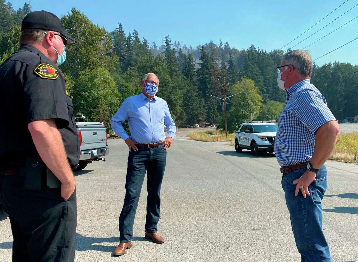 Washington Gov. Jay Inslee, center, talks to East Pierce Fire & Rescue Chief Bud Backer, left, and Pierce County Executive Bruce Dammeier about wildfires in the area, Wednesday, Sept. 9, 2020 in Sumner, Wash. Windblown wildfires raging across the Pacific Northwest destroyed hundreds of homes in Oregon, the governor said Wednesday, warning: