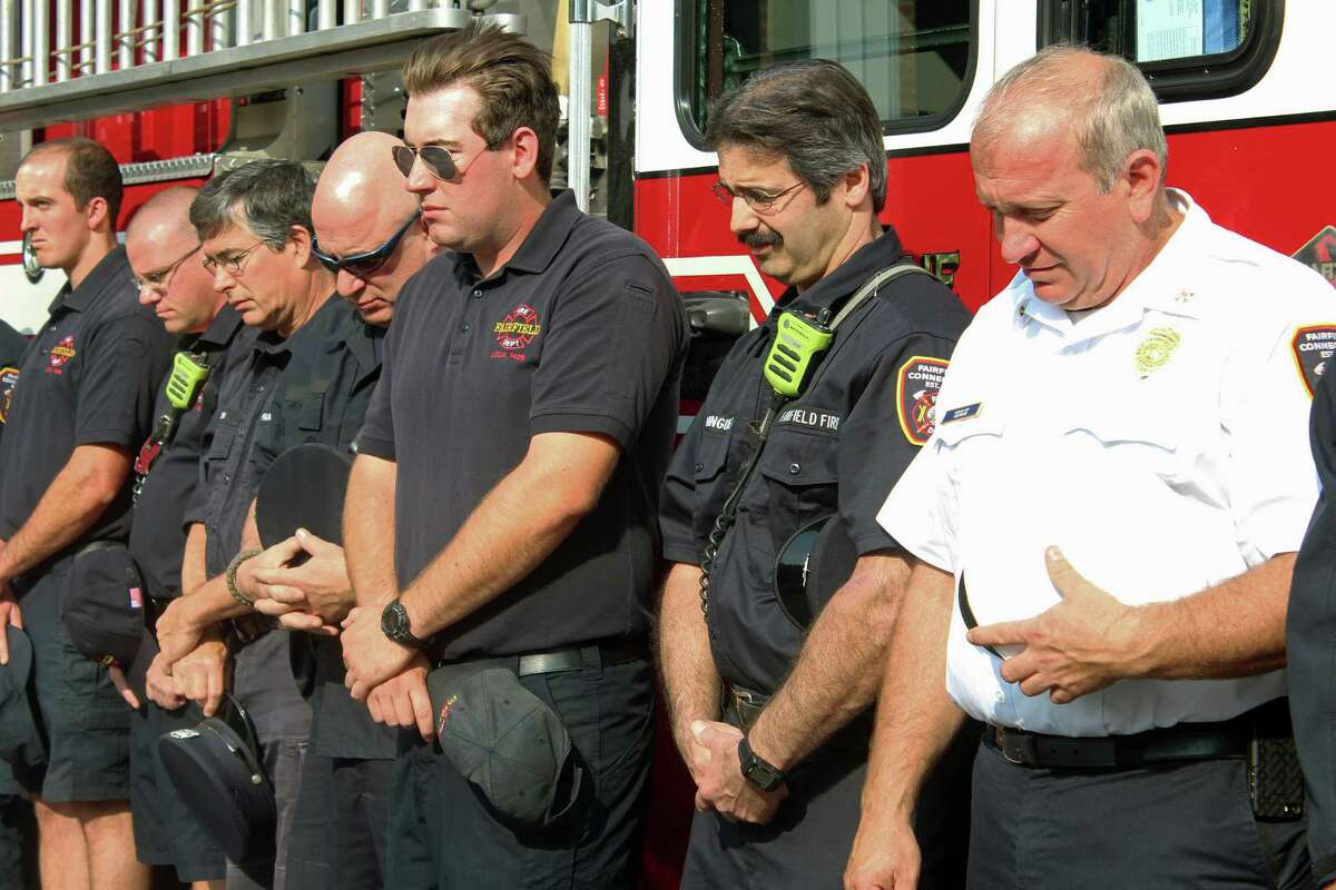 Firefighters bow their heads during a prayer at the town's annual Sept. 11 ceremony Monday at fire headquarters on Reef Road. Fairfield,CT. 9/11/17