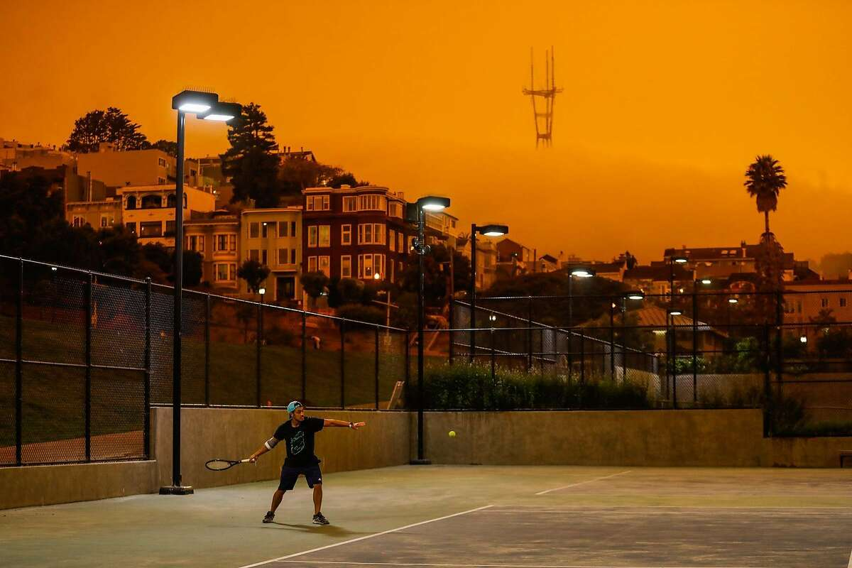 Shrouded by wildfire smoke filtered light Jonathan Risos plays tennis with a friend at Dolores Park on Wednesday, Sept. 9, 2020 in San Francisco, California.