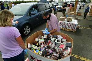 Volunteers hand out food during drive-through food distribution by Connecticut Food Bank Wednesday at Veteran's Memorial Park in Norwalk. The event provided food to people in need equivalent to more than 50,000 meals.