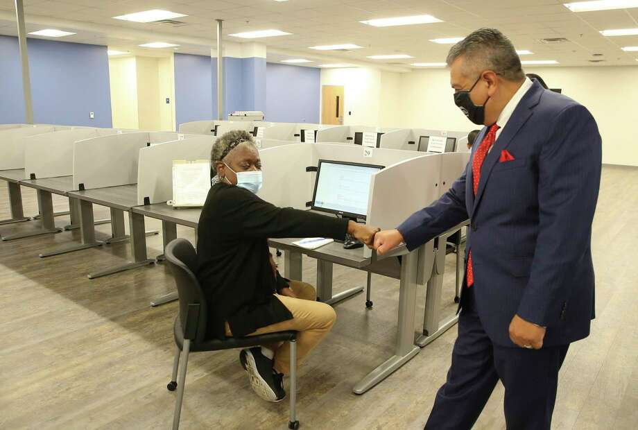 Workforce Solutions Alamo CEO Adrian Lopez (right) greets Sandra Campbell as she uses a computer to seek job opportunities. Workforce Solutions Alamo acts as the lead for intake and as a clearinghouse for job applicants. Lopez was at the organization's newest center where, due to the pandemic and safety protocols, are accepting appointments only for job applicants to search for potential work in the area. Photo: Kin Man Hui, San Antonio Express-News / Staff Photographer / **MANDATORY CREDIT FOR PHOTOGRAPHER AND SAN ANTONIO EXPRESS-NEWS/NO SALES/MAGS OUT/ TV OUT