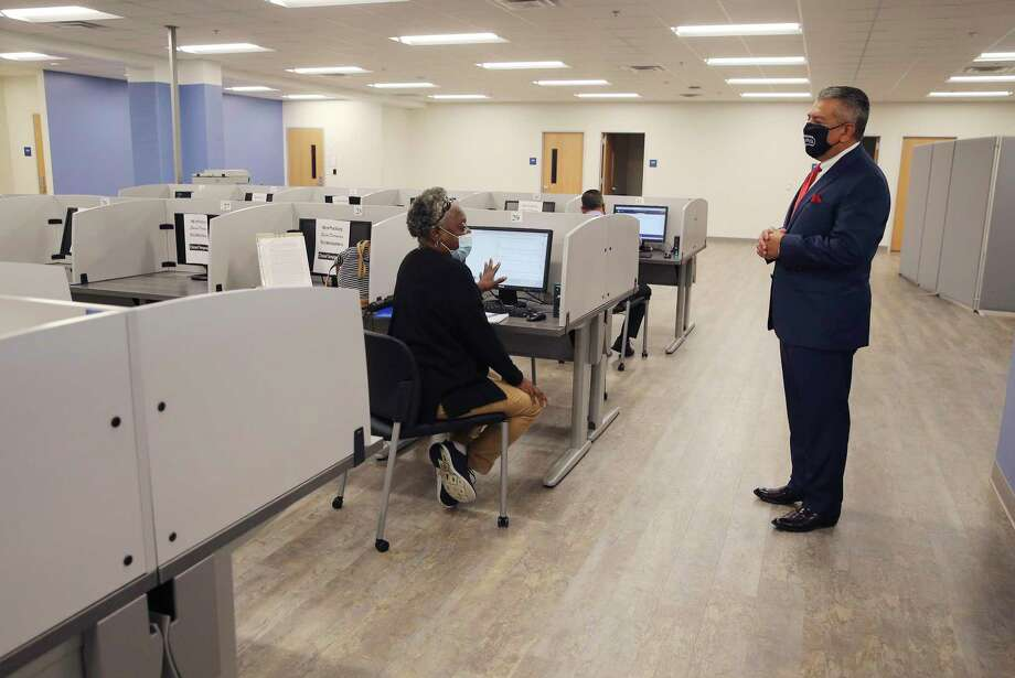 Workforce Solutions Alamo CEO Adrian Lopez (right) meets with Sandra Campbell as she uses a computer to seek job opportunities. Workforce Solutions Alamo acts as the lead for intake and as a clearinghouse for job applicants. Lopez was at the organization's newest center where, due to the pandemic and safety protocols, are accepting appointments only for job applicants to search for potential work in the area. Photo: Kin Man Hui, San Antonio Express-News / Staff Photographer / **MANDATORY CREDIT FOR PHOTOGRAPHER AND SAN ANTONIO EXPRESS-NEWS/NO SALES/MAGS OUT/ TV OUT