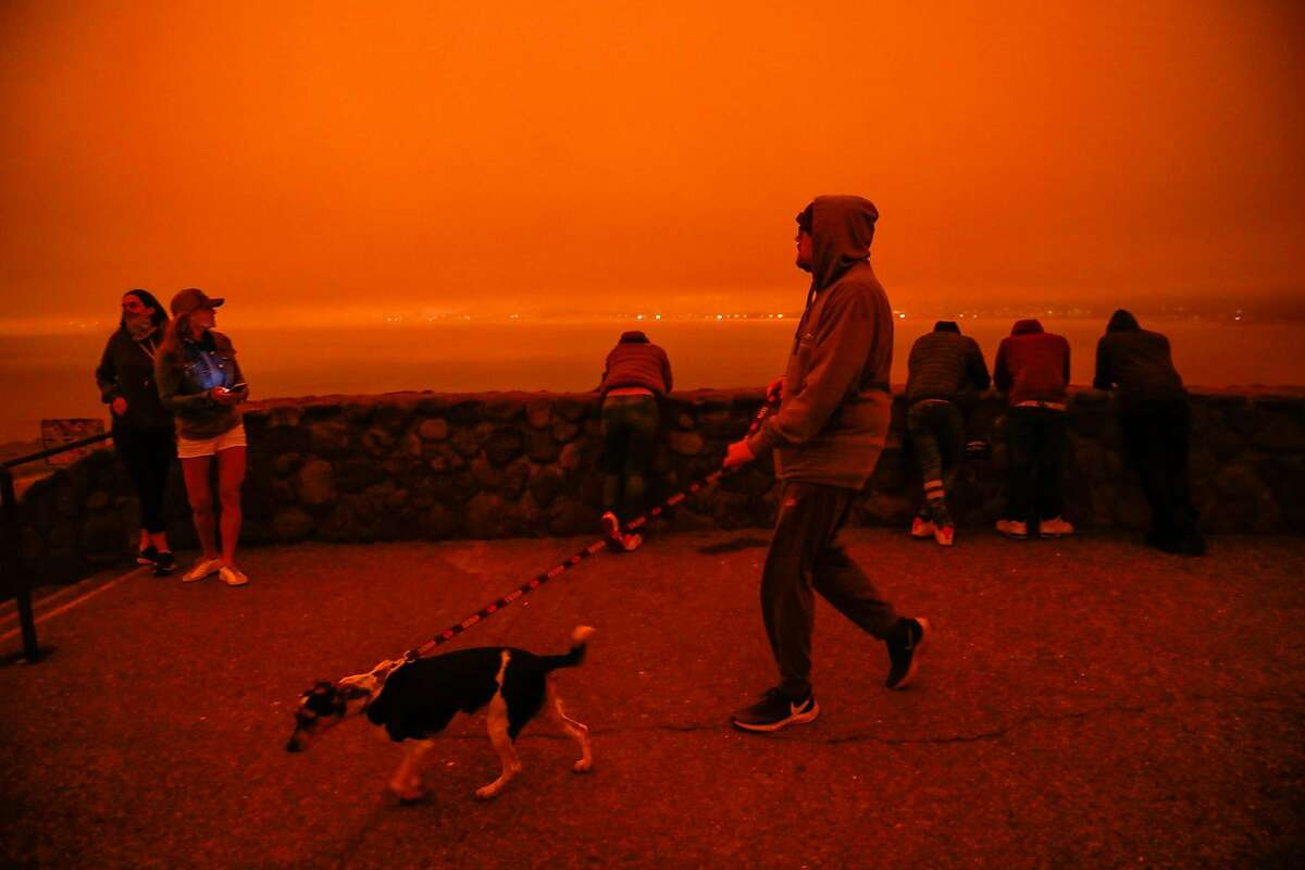 People hang out at an overlook at Golden Gate Bridge which was shrouded in dark orange smoke in Saulsalito, Calif. Wednesday, September 9, 2020 due to multiple wildfires burning across California and Oregon.