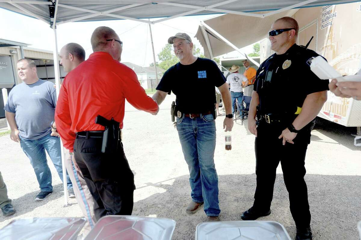 Bridge City Police Capt. Richard Teague greets Beaumont Police Officers Association Vice President Kane Dean as West Orange police officer David Vaugh looks on as they they gather for BPOA's meals for first responders in Orange County at the West Orange Fire Department Wednesday. Photo taken Wednesday, September 9, 2020 Kim Brent/The Enterprise