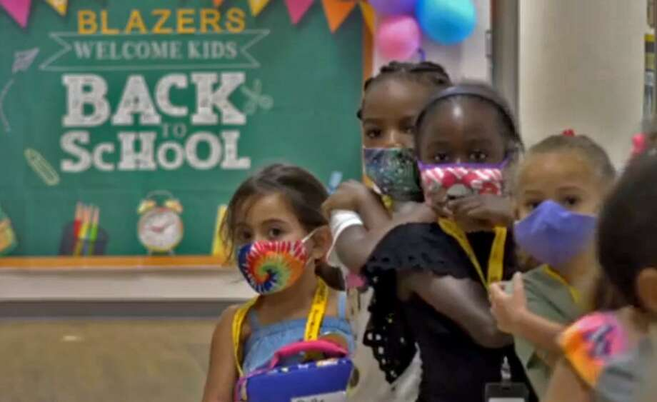 A group of Lamar CISD students wearing face coverings are shown in a back-to-school video posted to the district website on Sept. 8. Lamar, which resumed in-person classes on Aug. 24 with about 21,700 people on campuses, is reporting 12 active cases of COVID-19 among students who spent time on school grounds and seven active cases among staff members. Photo: Lamar CISD