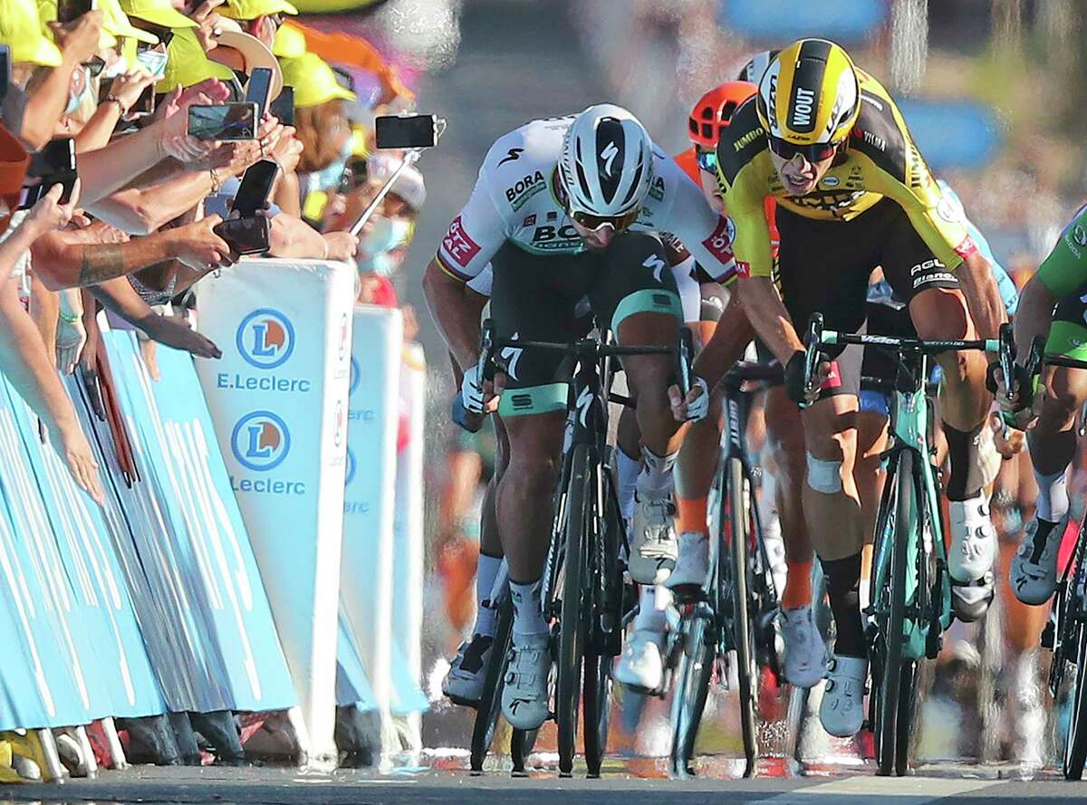 Slovakia's Peter Sagan, left, who originally came in second place, but was disqualified for a clash with Belgium's Wout Van Aert, right, races to the finish line of stage 11 of the Tour de France cycling race over 167.5 kilometers from Chatelaillon-Plage to Poitiers Wednesday, Sept. 9, 2020.(Thibault Camus/Pool)