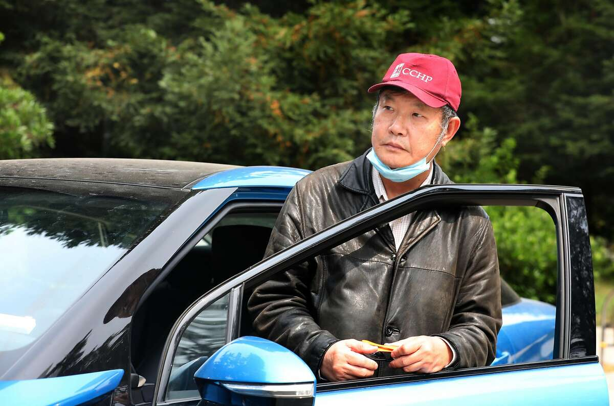 Jian Xiao, 64, was laid off from a job as a cook at the Calif. Academy of Sciences and also stopped his part-time Uber driving and is seen in his Uber car across from the employee entrance to the museum at Golden Gate park on Tuesday, Sept. 1, 2020, in San Francisco, Calif.