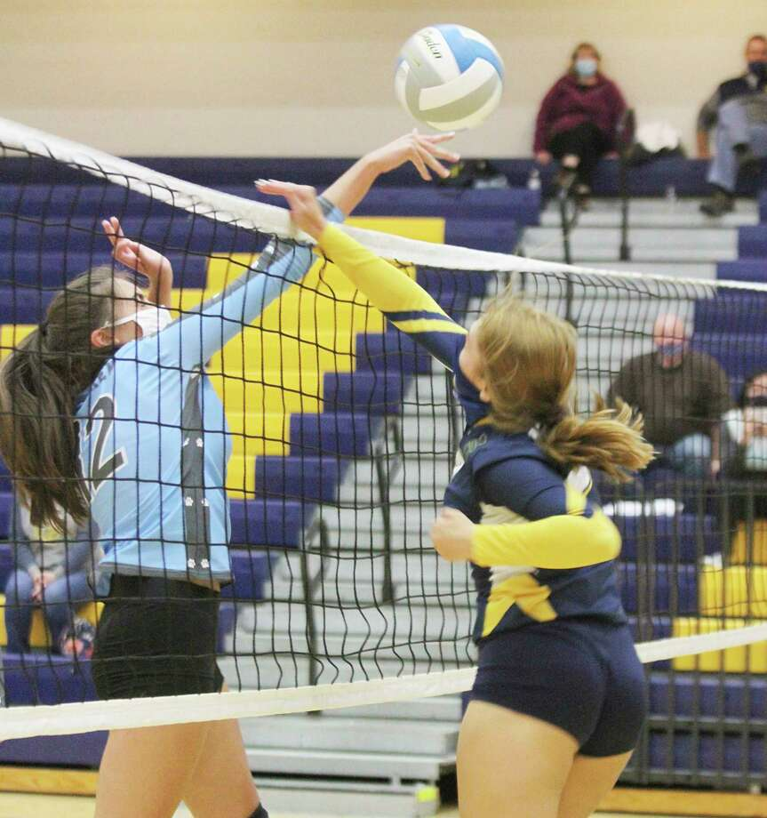 Brethren's Allyson Osga, left, and Manistee's Emma Bevans meet at the net Wednesday at Manistee. (Dylan Savela/News Advocate)