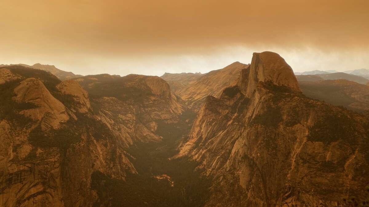 Half Dome is eerie yet beautiful beneath a smoky orange sky.