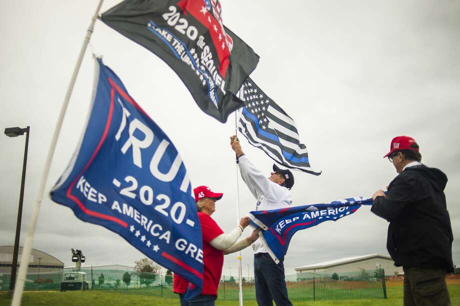 From left, Carole Nunn of Midland, Rick Frazier of Ohio and Blake Marnell of California raise a flag as supporters of President Donald Trump camp out overnight at MBS International Airport in Freeland Wednesday, Sept. 9, 2020, in the hopes of being one of the first in line for the President's campaign rally Thursday evening. (Katy Kildee/kkildee@mdn.net) Photo: (Katy Kildee/kkildee@mdn.net)