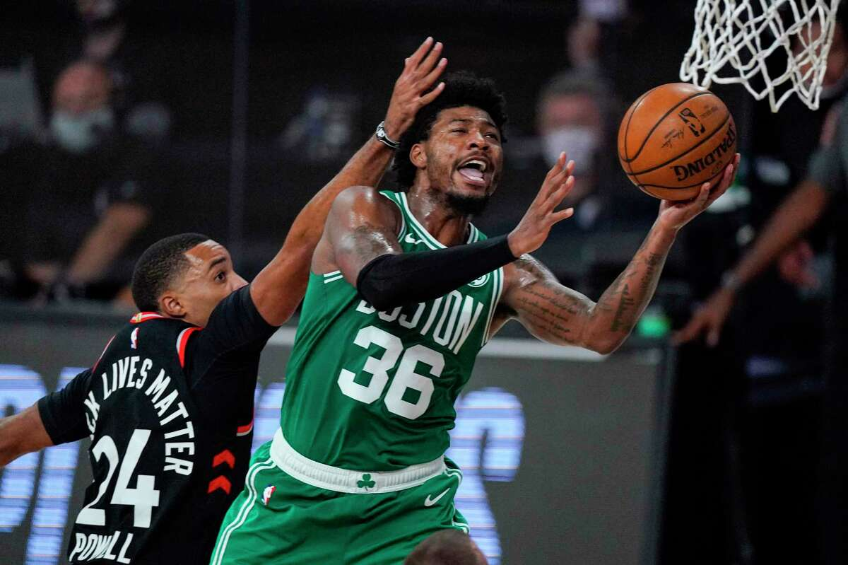 Boston Celtics guard Marcus Smart (36) shoots in front of Toronto Raptors guard Norman Powell (24) during the second half of an NBA conference semifinal playoff basketball game Wednesday, Sept. 9, 2020, in Lake Buena Vista, Fla. (AP Photo/Mark J. Terrill)