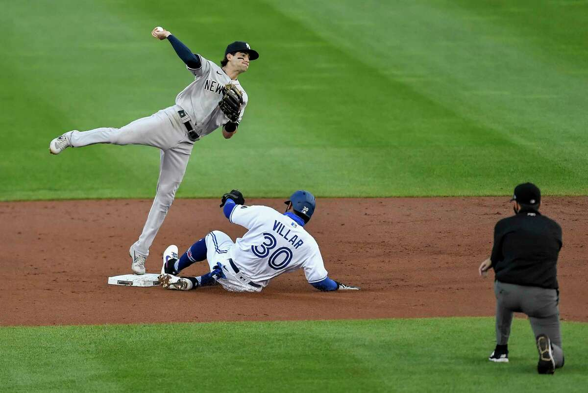 New York Yankees second baseman Tyler Wade, left, forces out Toronto Blue Jays' Jonathan Villar (30) at second and throws to first on a ball hit by Caleb Joseph, who was safe during the second inning of a baseball game in Buffalo, N.Y., Wednesday, Sept. 9, 2020. (AP Photo/Adrian Kraus)