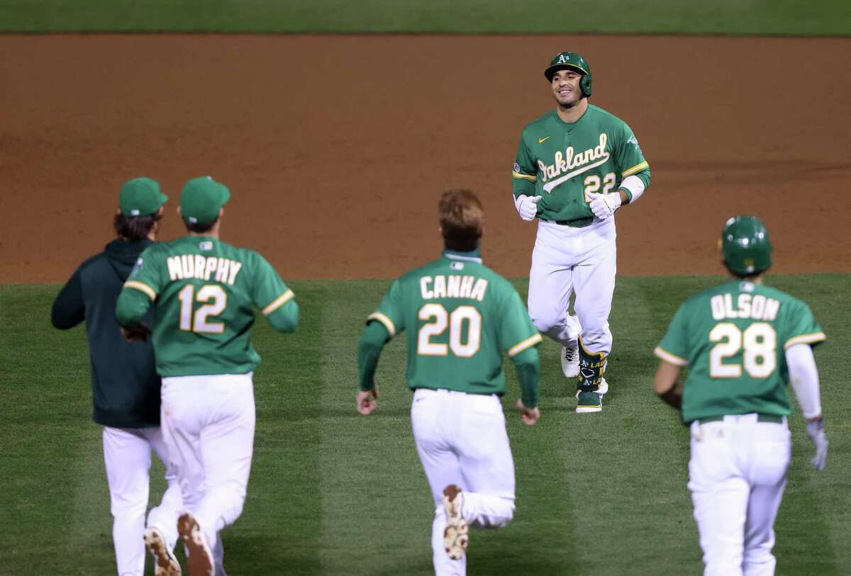 OAKLAND, CALIFORNIA - SEPTEMBER 09: Ramon Laureano #22 of the Oakland Athletics is congratulated by teammates after hitting the game-winning hit in the bottom of the ninth inning against the Houston Astros at RingCentral Coliseum on September 09, 2020 in Oakland, California.