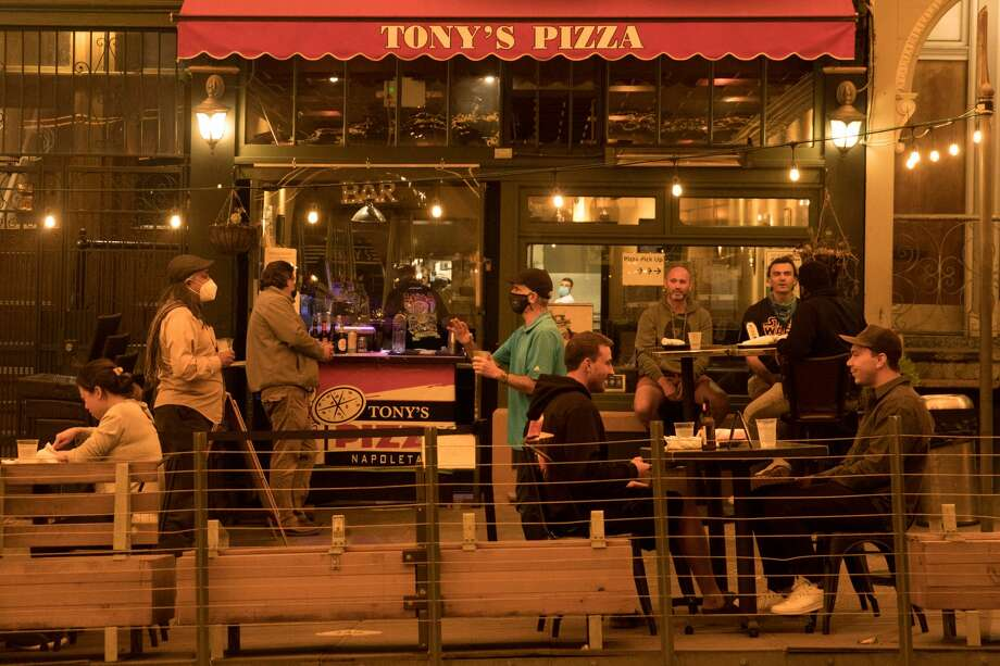 Customers eater meals outside Tony's Pizza in North Beach. Smoke from wildfires in California and Oregon spread over San Francisco on Sept. 9, 2020 darkening the skies to an orange hue. Photo: Douglas Zimmerman/SFGATE / SFGATE