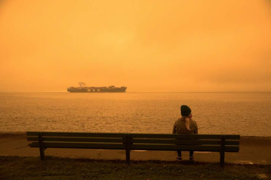 A woman wearing a mask sits on a bench taking in the unusual conditions. Smoke from wildfires in California and Oregon spread over San Francisco on Sept. 9, 2020 darkening the skies to an orange hue. Photo: Douglas Zimmerman/SFGATE / SFGATE
