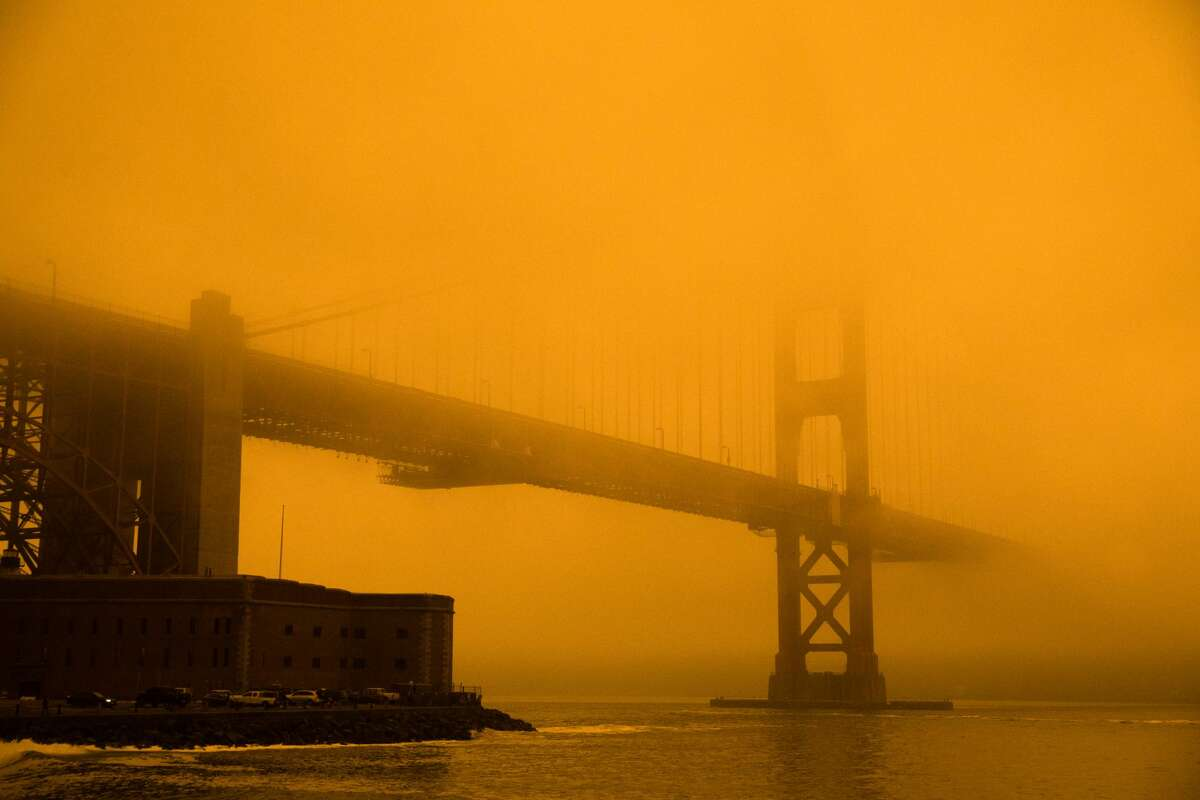 The Golden Gate Bridge is covered in orange-tinged smoke and fog. Smoke from wildfires in California and Oregon spread over San Francisco on Sept. 9, 2020 darkening the skies to an orange hue.