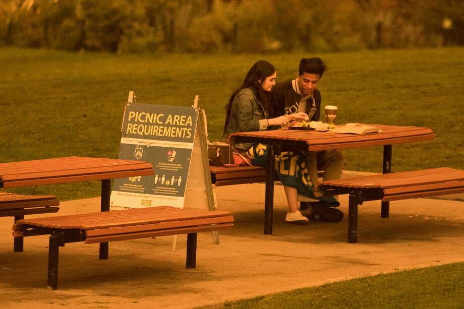 A couple eats a meal at Dolores Park. Smoke from wildfires in California and Oregon spread over San Francisco on Sept. 9, 2020 darkening the skies to an orange hue. Photo: Douglas Zimmerman/SFGATE / SFGATE